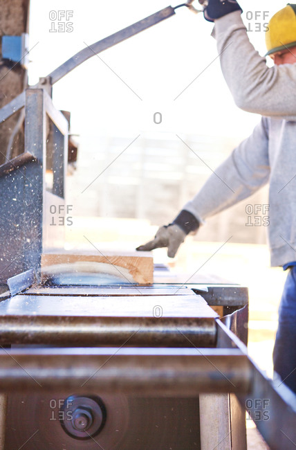 Carpenter using a table saw at a woodshop