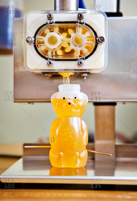 Machine dispensing honey into plastic honey bear