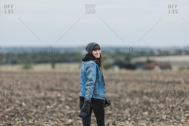 Woman looking over shoulder in barren farm field