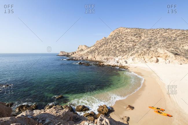 Kayaks on an empty beach in Chileno bay, Cabo San Lucas, Mexico