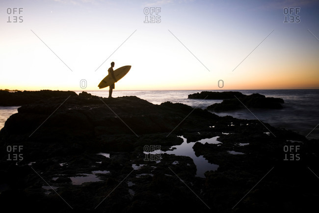 Man holding a surfboard on the beach at sunset
