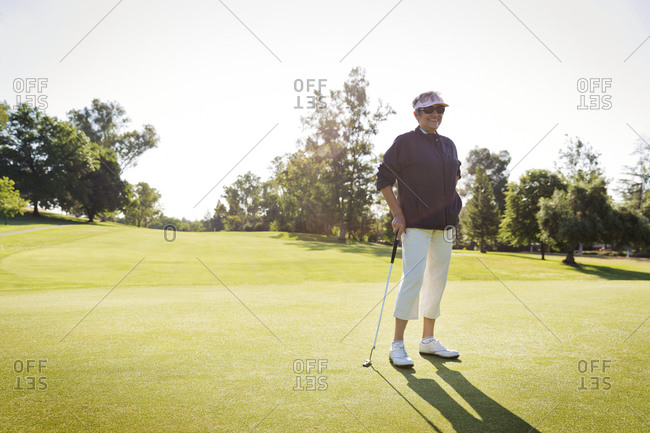 A woman smiling on a golf course