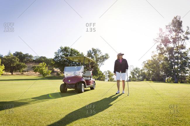 A woman stands next to a golf cart