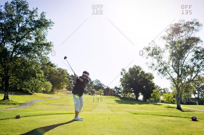 A woman swings a golf club