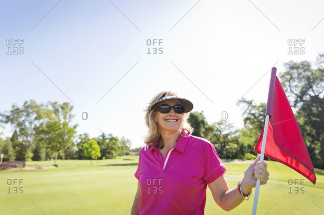 A golfer holds a flag on the green