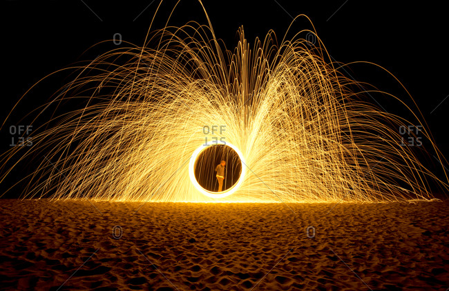 A twirling firework exploding on a beach