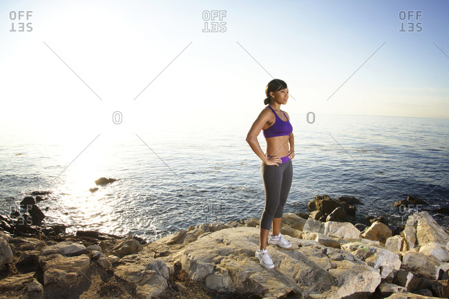 A woman takes a break from her workout on a rocky coast