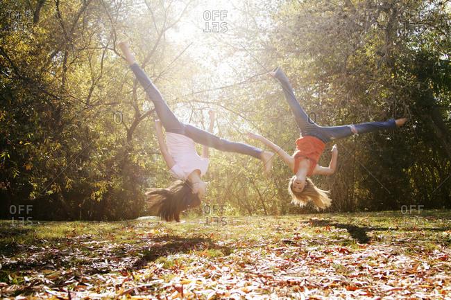 Two young women flip upside-down outside