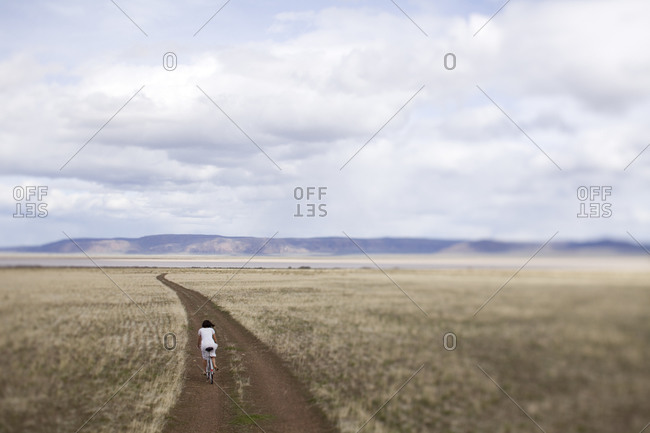 Woman riding a bike on a desolate dirt road