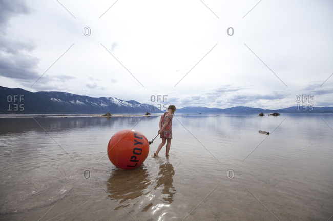 A young girl dragging a big buoy she found in shallow water along the shore of Lake Pend Oreille