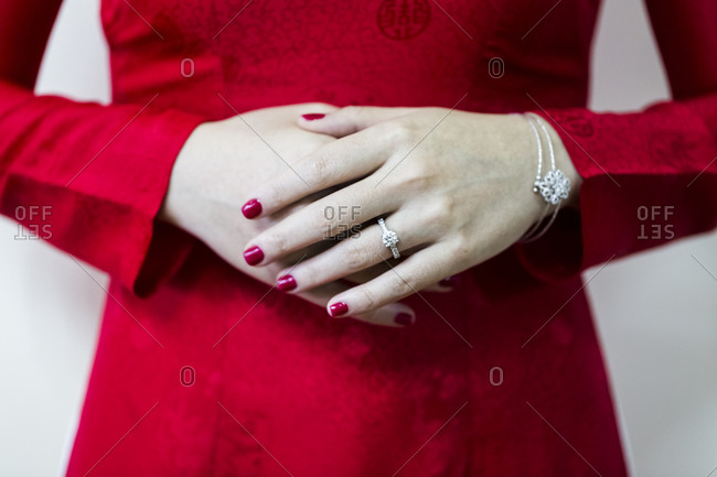 The hands of a young Vietnamese bride in a red ao dai