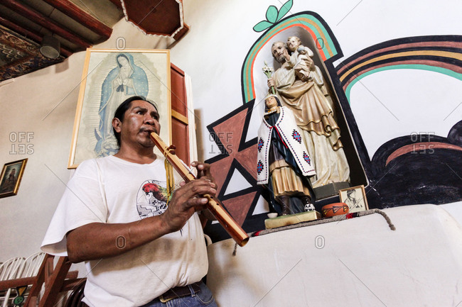 Laguna Pueblo, NM, USA - Circa 2010: Local Laguna Pueblo Native American plays the flute in the first Catholic church on Native land. The statue of St. Kitari sits on the altar.