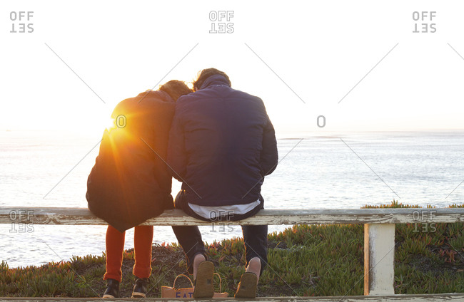 Couple sitting on a fence overlooking the Pacific Ocean at sunset