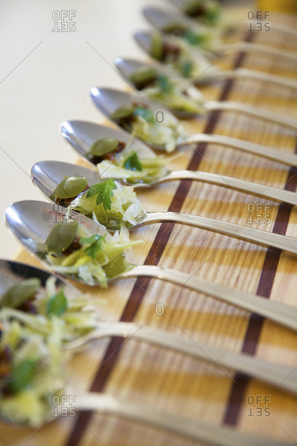Spoons lined up and loaded with a vegetable amuse bouche