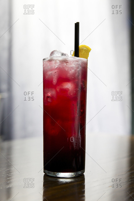 Collins glass with lemon-garnished fruity cocktail