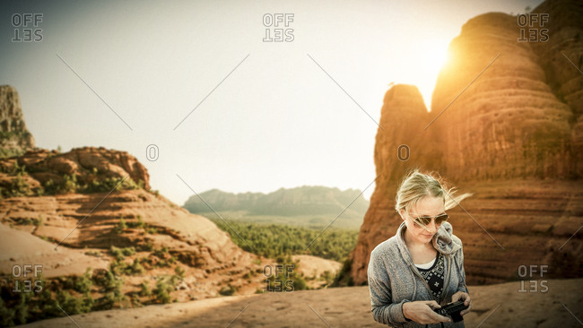 A woman in the desert looks at her camera