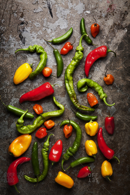An arrangement of peppers on a stone surface