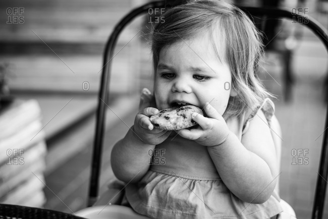 Little girl biting into a cookie