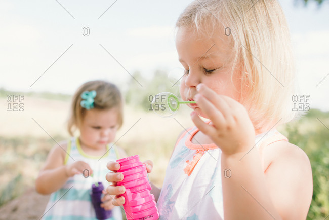 Sisters blowing soap bubbles