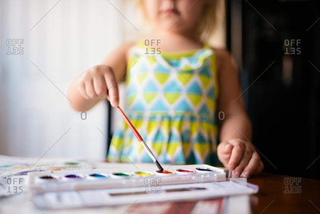 Young girl painting with watercolors