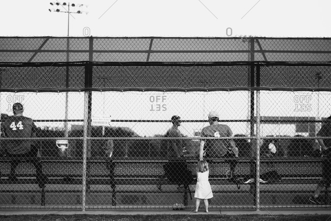 Young girl standing outside of a baseball field