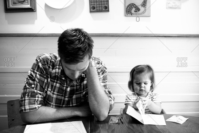 Young girl reading with his father at a table