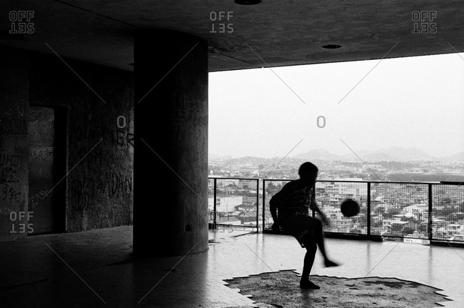 Silhouette of child playing soccer in an abandoned building