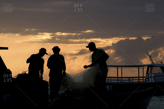 Silhouette of a fishermen at sunset in Brazil&#10,