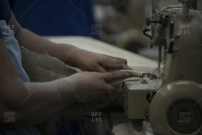 Woman sewing burlap in a textile factory