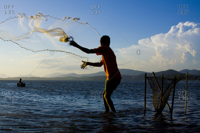 Fisherman fishing with net