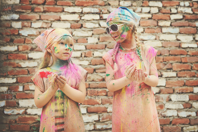 Two girls covered in colorful powder for the Hindu festival of Holi