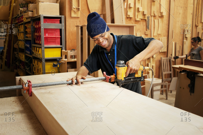 Furniture maker building a table in factory