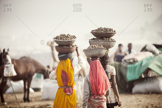 Women carrying food in large bowls balanced on their heads