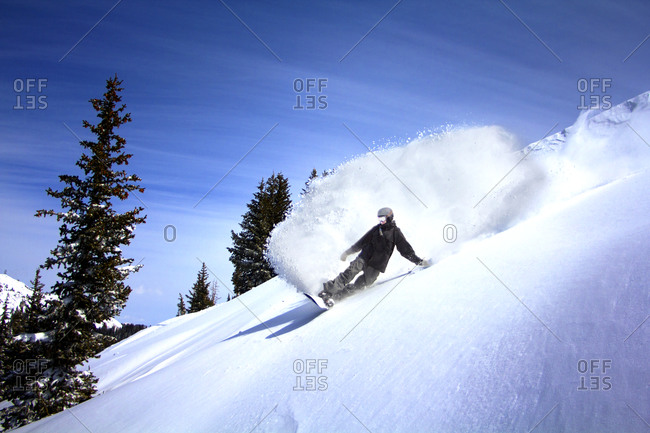Snowboarder riding down slope