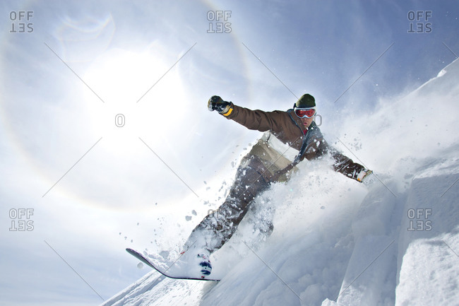 Man snowboarding through fresh powder