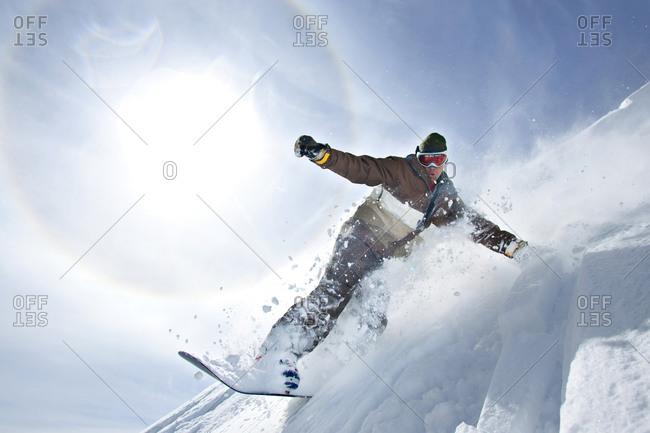 Man snowboarding through fresh powder