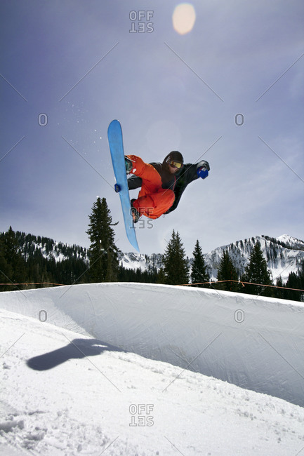 Snowboarder doing a trick in a half pipe