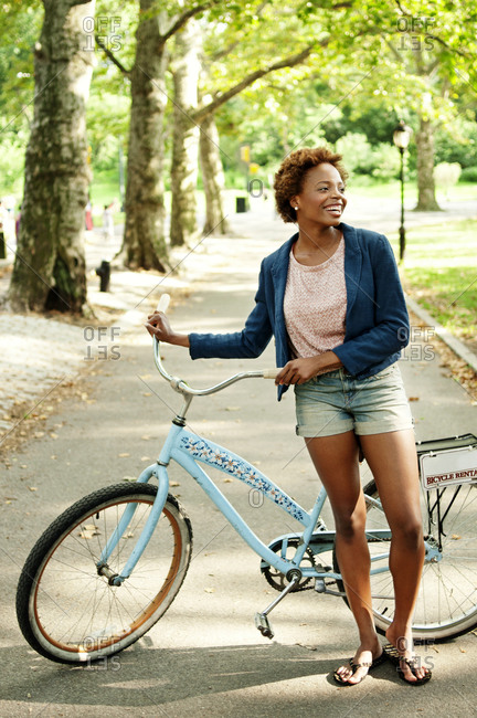 Young woman with a bike in a park