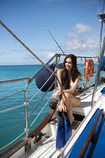 Woman with fins seated on deck of sailboat