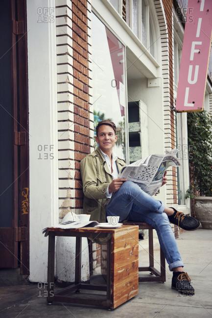 Man reading newspaper outside a café