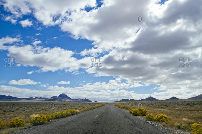 Desert road leading toward mountains