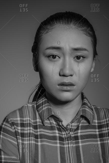 Studio shot of young Asian man crying