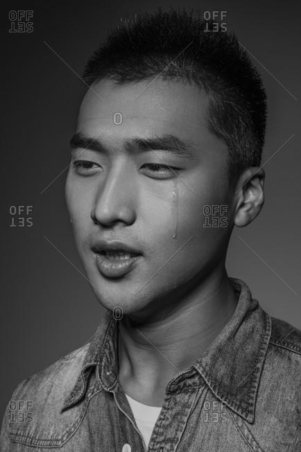 Asian man crying in studio shot