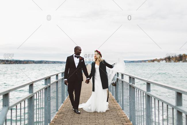 Newlywed couple walking on dock after wedding