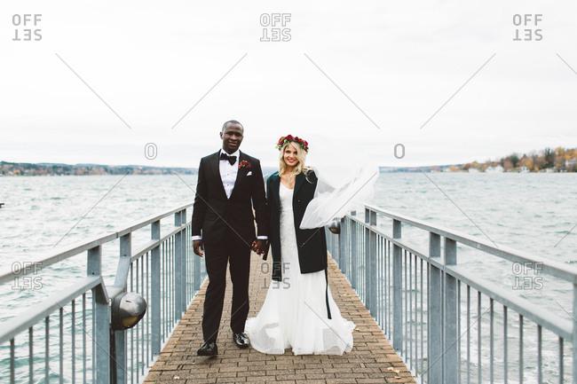 b3a2112633e799 A bride and groom walk down a pier stock photo - OFFSET