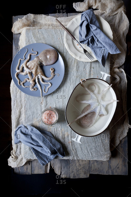 Two small whole octopus on a rustic table