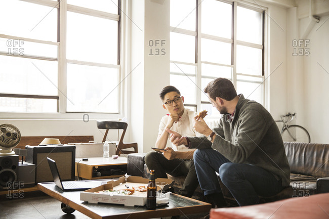 Two young businessmen collaborating over pizza and beer