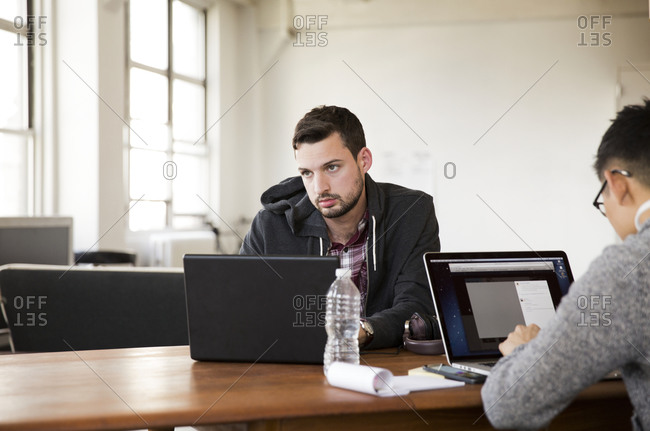 Two young businessmen collaborating with laptop