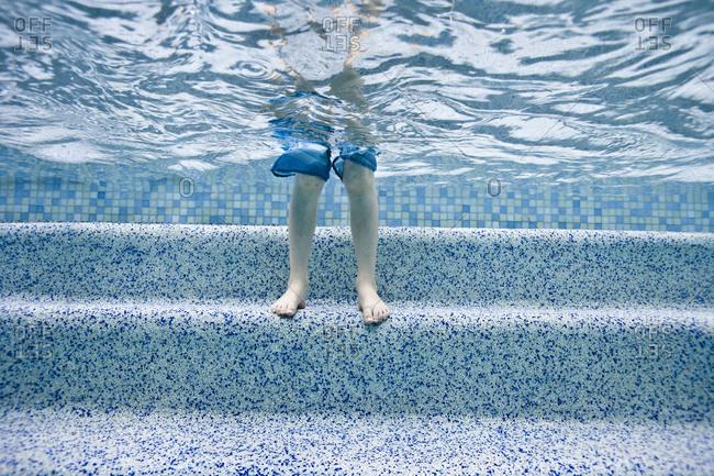 Feet and legs on steps underwater in pool