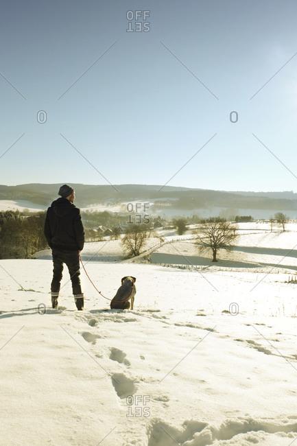 Man walking dog in winter landscape